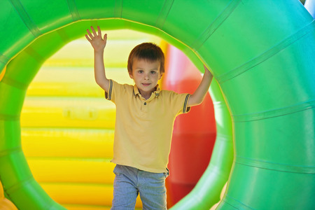 person outdoors: Cute little boy, playing in a rolling plastic cylinder ring, full with air, outdoor