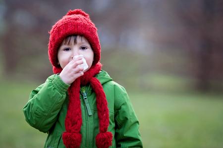 nariz: El ni�o peque�o, estornudos y son�ndose la nariz al aire libre en un d�a soleado de invierno