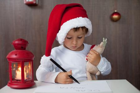 산타에게 편지를 쓰고 사랑스러운 작은 소년,