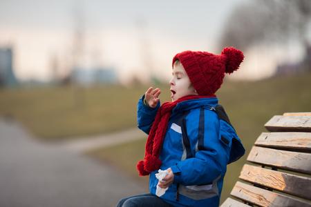 Kleine jongen, niezen en blazen zijn neus buiten op een zonnige winterse dag, zittend op een bankje