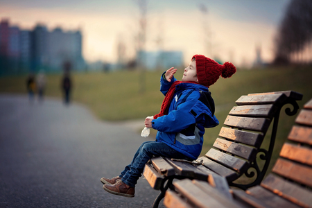 allergy: Little boy, sneezing and blowing his nose outdoor on a sunny winter day, sitting on a bench Stock Photo