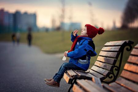 nariz: Niño pequeño, estornudar y sonarse la nariz al aire libre en un día soleado de invierno, sentado en un banco Foto de archivo