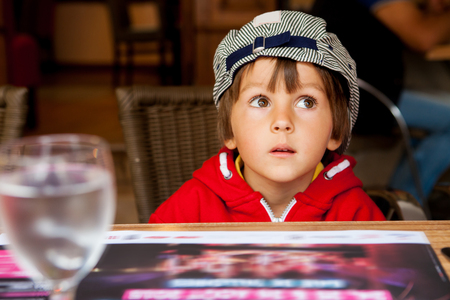 facial expression: Close portrait of Handsome Young Boy with flat cap, wondering and looking away, outdoors Stock Photo
