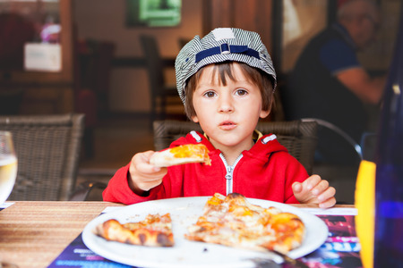 hungry children: Sweet adorable child, boy, eating pizza at a restaurant, , summertime