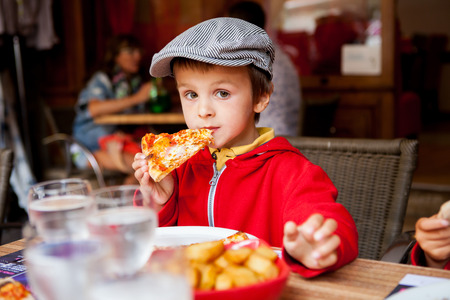 people eating restaurant: Sweet adorable child, boy, eating pizza at a restaurant, , summertime