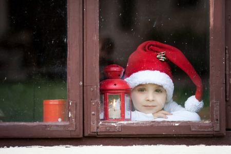 looking through window: Adorable boy, looking through window, waiting for Santa Stock Photo