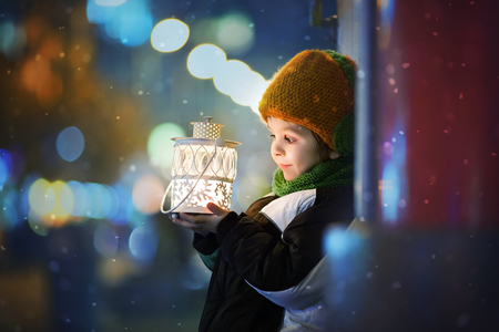 かわいい男の子、ランタンを屋外に保持、冬