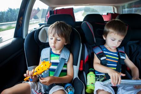 Twee jongen in autozitjes voor kinderen, reizen met de auto en het spelen met speelgoed en tablet, zomer