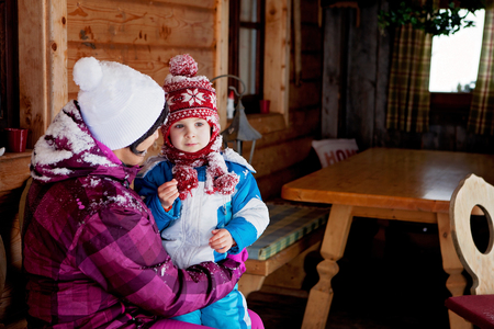 two generation family: Young grandmother and her little toddler grandson, playing in the snow, colorful clothing Stock Photo