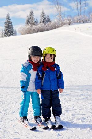 resfriado: Retrato de dos lindos ni�os peque�os, hermanos, a esquiar juntos en un d�a soleado