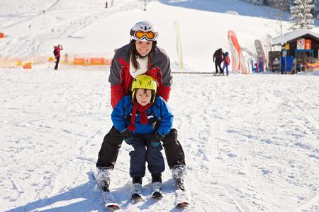 Mooie jonge moeder en haar peuter jongen, skiën in de bergen, de winter tijd
