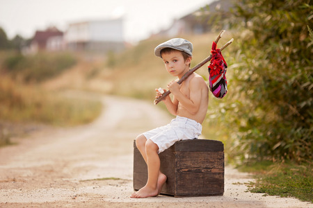 bare feet boys: Cute little boy, sitting on a big old suitcase, vintage, holding a bundle, eating bread and smiling