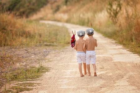 bare feet boys: Two cute little boys,brothers, holding a bundle, eating bread and smiling, walking bare feet on a dusty rural road Stock Photo