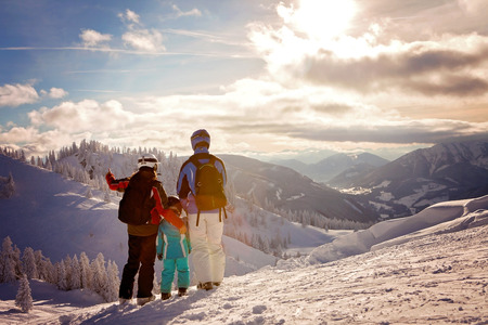 Happy family in winter clothing at the ski resort, winter time, watching at mountains in front of them Banco de Imagens