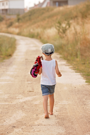 bare feet boys: Cute little boys, holding a bundle, eating bread, walking bare feet on a dusty rural road Stock Photo