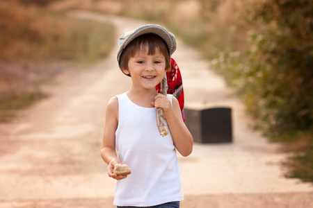 bare feet boys: Cute little boys, holding a bundle, eating bread and smiling, walking bare feet on a dusty rural road Stock Photo
