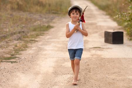Carino ragazzini, in possesso di un pacco, mangiando pane e sorridente, camminare a piedi nudi su una strada rurale polverosa