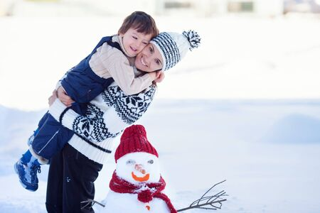 frosty the snowman: Happy beautiful family building snowman in garden, winter time, mom and kid Stock Photo