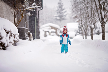 either: Happy little boy in a snowsuit, hat and scarf, walking through a snowy path with deep snow banks on either side, next to row of houses Stock Photo
