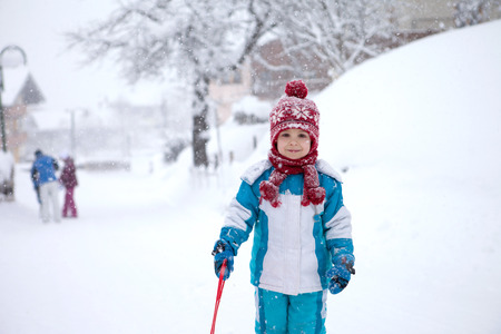 sledging people: Cute little boy in blue winter suit, playing outdoor in the snow, wintertime Stock Photo