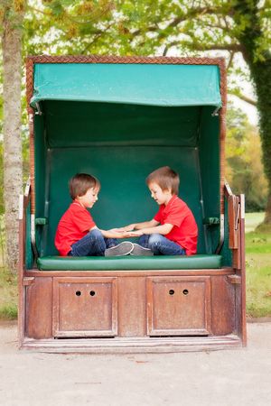 sheltered: Two kids, brothers,sitting in a sheltered bench, playing hand clapping game, outdoors in the summer