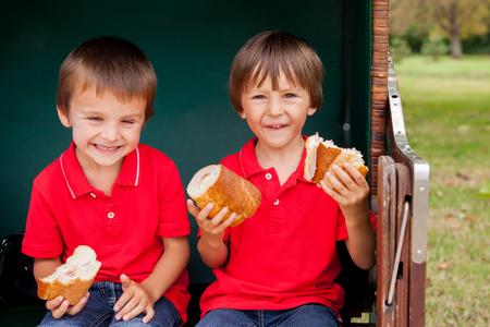 sheltered: Two kids, sitting in a sheltered bench, eating sandwiches, outdoor summertime