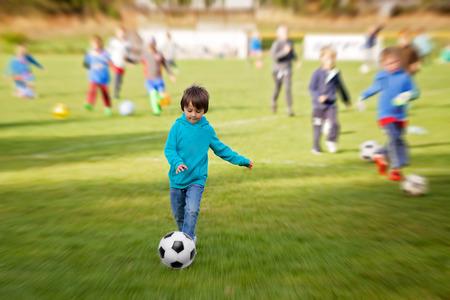 Grupo de niños, jugar al fútbol, ??hacer ejercicio al aire libre, desenfoque radial aplicada Foto de archivo