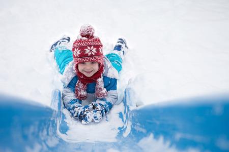 sledging people: Cute little boy, going down a snowy slide