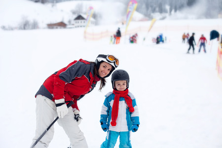 cool kids: Beautiful young mom and her toddler boy, skiing in the mountains, winter time Stock Photo
