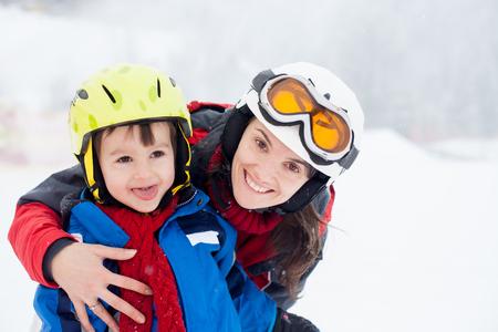 美しい若いお母さんおよび彼女の幼児男の子、スキー山で冬時間
