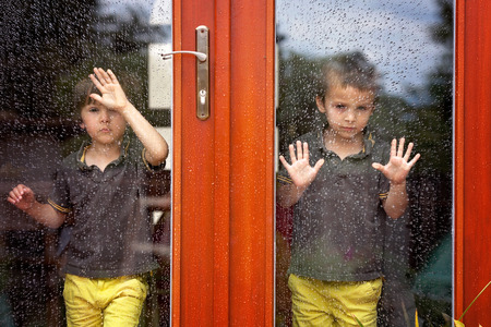 Twee kleine jongen, het dragen van dezelfde kleren kijken door een grote glazen deur van de regen buiten, summertime Stockfoto