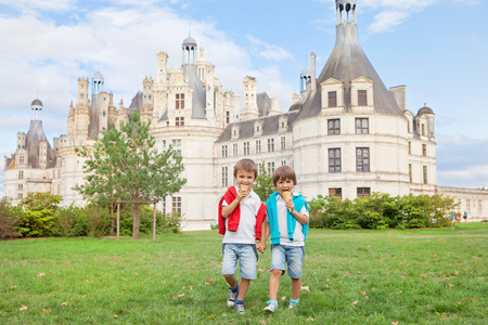 Two adorable boys in casual clothing, eating ice cream sitting on a lawn in front of the biggest castle along the Loire river, Chambord, on sunset, castle magnificently arousing behind them