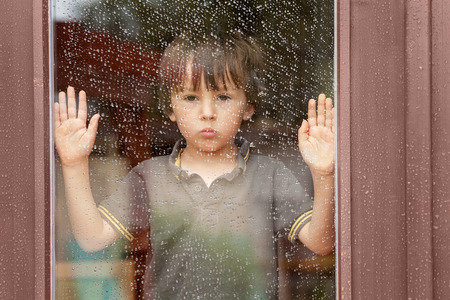 Little boy behind the window in the rain, looking sad Stockfoto