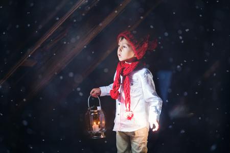 Lieve jongen, met een lantaarn, kijken naar een licht door een raam, staande in de sneeuw, in openlucht