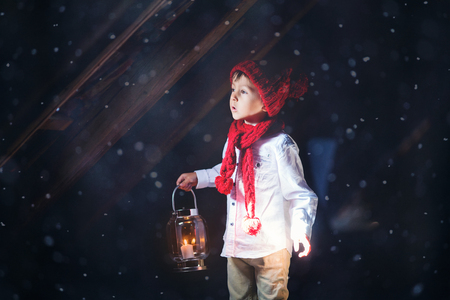 Sweet boy, holding a lantern, looking at a light coming through a window, standing in the snow, outdoors Stock Photo