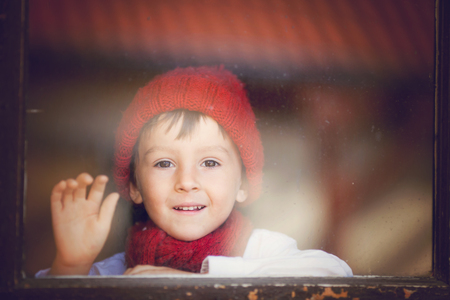 waiting glance: Portrait of little boy, child behind the window, wearing hat and scarf, looking outdoor
