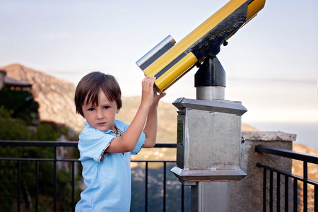 experimenting: Curious boy, looking through a telescope at something interesting, summertime Stock Photo