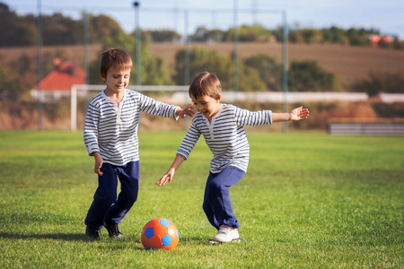 sporting goods: Two cute little boys, playing football outdoor, autumn time