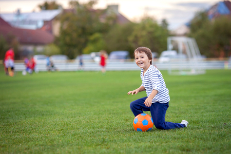 Little toddler boy playing soccer and football, having fun outdoors on sunset on the playground.Active children, autumn day