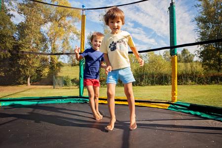Twee zoete kinderen, broers, springen op een trampoline, zomer, plezier maken. Actieve kinderen Stockfoto