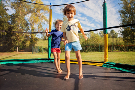 Two sweet kids, brothers, jumping on a trampoline, summertime, having fun. Active children