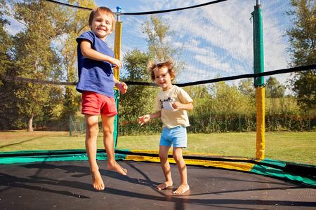 두 달콤한 아이, 형제, 트램 폴 린, 여름철, 재미에 점프. 활동적인 아이들 스톡 콘텐츠