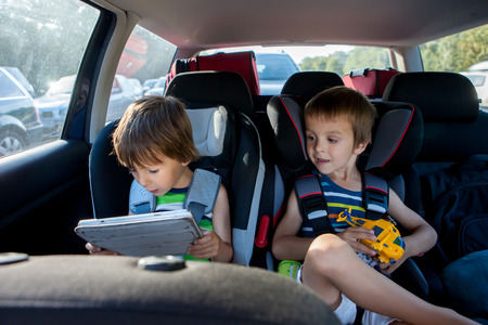 restraints: Two boy in children car seats, traveling by car and playing with toys and tablet, summertime