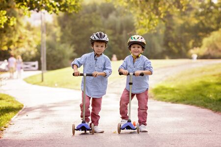 scooter: Two cute boys, compete in riding scooters, outdoor in the park, summertime on sunset Stock Photo
