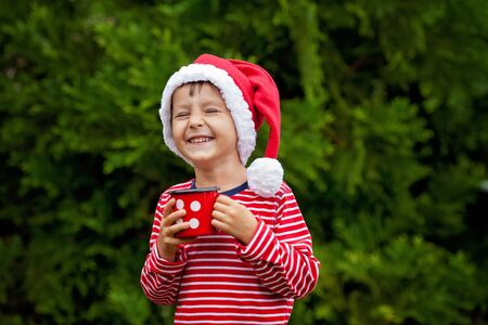 jungle boy: Sweet boy in striped shirt with santa hat, holding cup with tea outdoors, wintertime, happiness concept