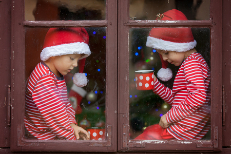 red tea: Two cute boys, brothers, looking through a window, drinking tea and waiting impatiently for Santa. Christmas concept