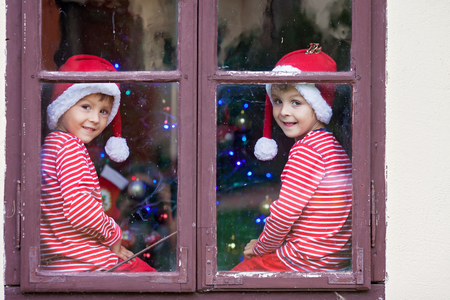 beautiful little boys: Two cute boys, brothers, looking through a window, waiting impatiently for Santa, Christmas concept