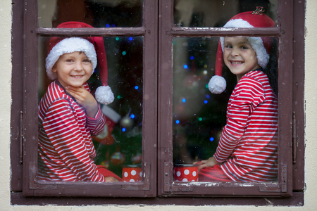 christmas tea: Two cute boys, brothers, looking through a window, drinking tea and waiting impatiently for Santa. Christmas concept