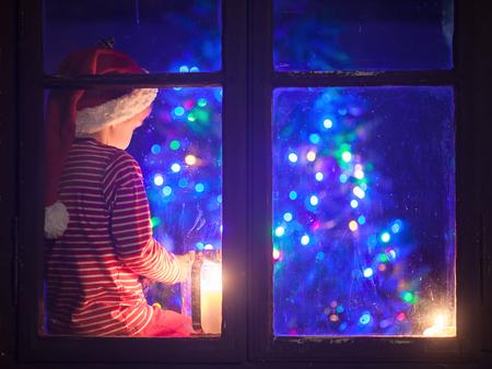 Cute boy, assis sur un bouclier de la fenêtre, en jouant sur le téléphone portable dans la nuit, le temps de Noël, en attendant le Père Noël