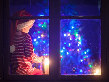 young child: Cute boy, sitting on a window shield, playing on mobile phone at night, christmas time, waiting for Santa Claus Stock Photo